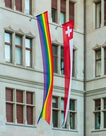 Zurich, Switzerland - June 16, 2019: facade of the Zurich City Hall building decorated with a rainbow flag of the LGBT movement and a flag of Switzerland for the Zurich Pride Festival which took place during June 14-15. Zurich City Hall houses the adminis Sajtókép