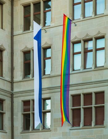 Zurich, Switzerland - June 16, 2019: facade of the Zurich City Hall building decorated with a rainbow flag of the LGBT movement and a flag of Zurich for the Zurich Pride Festival which took place during June 14-15. Zurich City Hall houses the administrati Sajtókép