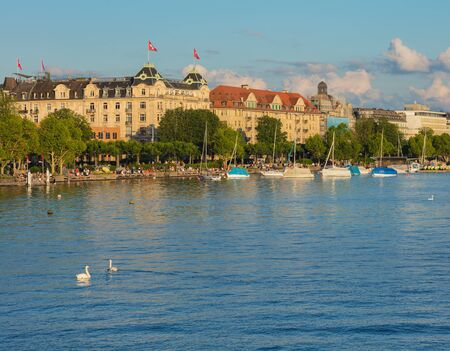 Zurich, Switzerland - June 16, 2019: Lake Zurich at sunset, people on its embankment, buildings of the city of Zurich in the background. Lake Zurich is a lake in Switzerland, extending southeast of the city of Zurich, which is the largest city of the coun