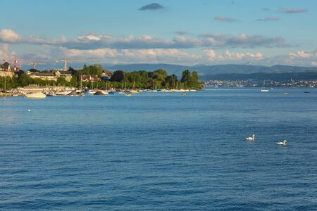 Zurich, Switzerland - June 16, 2019: Lake Zurich at sunset, people in boats, buildings of the city of Zurich, summits of the Alps in the background. Lake Zurich is a lake in Switzerland, extending southeast of the city of Zurich, which is the largest city
