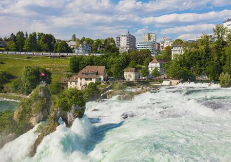 Laufen, Switzerland - June 7, 2019: the Rhine Falls waterfall as seen from the Laufen Castle, buildings of the town of Neuhausen am Rheinfall in the background. Laufen Castle (German: Schloss Laufen) is a castle in the municipality of Laufen-Uhwiesen in t