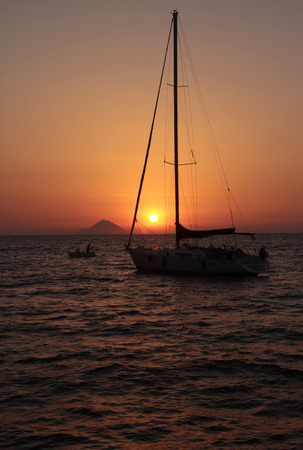 eolian islands: Sunset with sailboat in front of Stromboli volcano, Eolian islands, Sicily, Italy Stock Photo