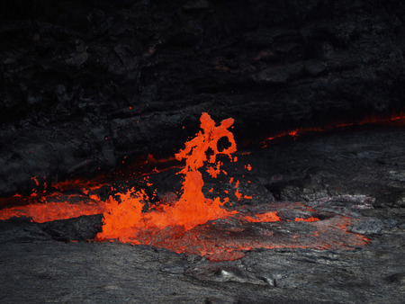 Lava burst inside the Erta Ale volcano. This lava lake is continuously flowing and bubbling inside this 60m-large crater. Located in Ethiopia, close to the border with Erithrea. photo