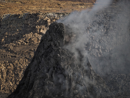 pinnacle: Smoking pinnacle in the Erta Ale volcano area. The lava flow formed incredible waves and patterns after each eruption. Located in Ethiopia, close to the border with Erithrea.