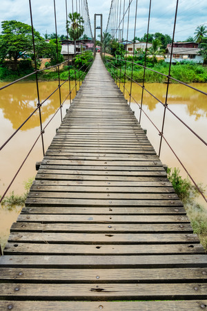 wonky: Rope suspension bridge across a river in flood, Thailand Stock Photo