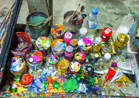 color palette: Brushes and cans of paint on a multicolored palette