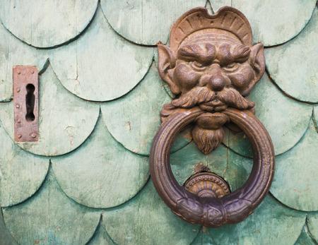 doorknocker: Iron goblin face doorknocker on green wooden door Stock Photo