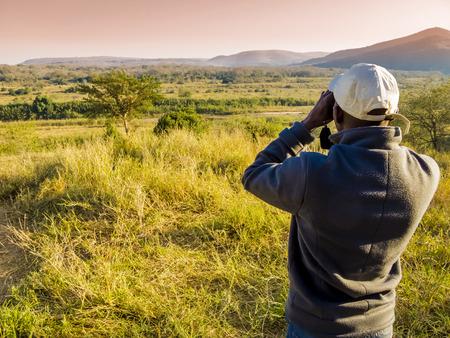 animales safari: Sudáfrica, guardabosques mirando a través de binoculares en busca de los animales durante un safari Foto de archivo