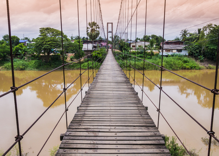 Rope suspension bridge across a river in flood at dusk, Thailand