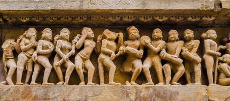 Stone carved bas-relief with dancers and musicians in erotic scenes, Kahjuraho temple, India