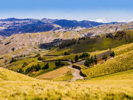 Ecuador, pintoresco paisaje andino entre el cañón de Zumbahua y la laguna de Quilotoa con camino de tierra y campos cultivados