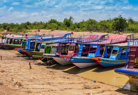Colorful tourist boats moored on river bank to explore Tonle Sap lake, Siem Reap Province, Cambodia