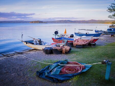 Row of typical fishermen boats docked on Marta beach, a little medieval village on Bolsena lakeshore, Viterbo province, Lazio, Italy