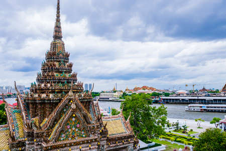 Stunning view of pagoda decorated with colorful tiles in Wat Arun complex, with Chao Phraya river in background, Bangkok, Thailand