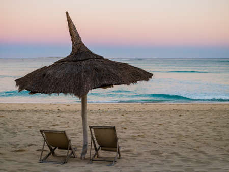 Stunning sunrise with a traditional straw beach umbrella and two deckchairs facing the peaceful Indian Ocean coast, Anakao, Madagascar