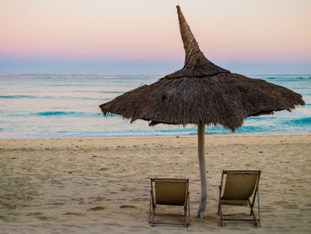 Traditional straw beach umbrella and two deckchairs facing the peaceful Indian Ocean coast, Anakao, Madagascar Reklamní fotografie