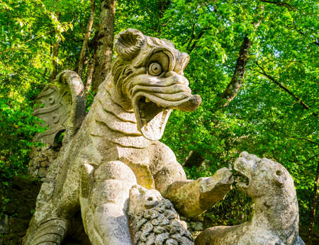 Detail of the winging dragon fighting against three beasts, a huge sculpture at famous Park of the Monsters, also named Sacred Grove, Bomarzo Gardens, province of Viterbo, Lazio, Italy