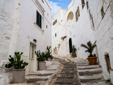 Ancient cobblestone alley with traditional white houses in Ostuni, Apulia region, southern Italy