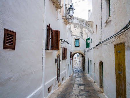 Picturesque cobblestone alley with traditional white houses in the ancient town of Ostuni, Apulia region, southern Italy