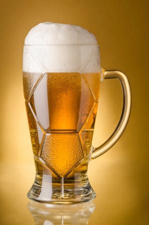 Glass of  light beerr on a yellow background Reklamní fotografie