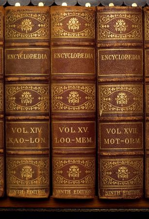 Three old encyclopedia books on bookshelf Standard-Bild