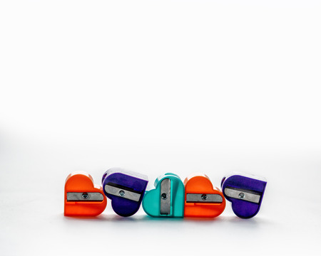 Five colorful pencil sharpeners in the shape of a heart on the white background. Front view. Banco de Imagens