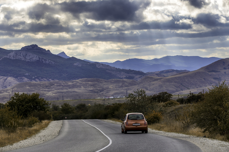 The red car travels along the highway, around a beautiful landscape. Bluish thunderous mountains under the sky covered with clouds Foto de archivo