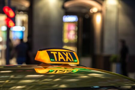 Yellow taxi sign at night in a metropolis. Place for the inscription, the concept of a modern city, comfort, dynamics, speed. Stock Photo