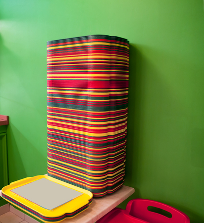 A stack of red, yellow, green trays on the table. Buffet, trays, standing in a pile before starting maintenance. Stock Photo