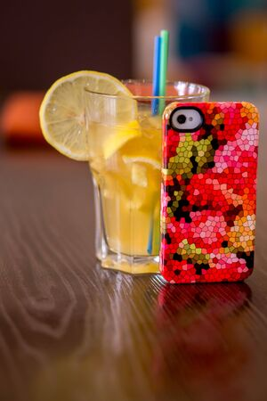 A bright multi-colored cell-phone cover on a table next to a juice coctail in a glass with a drinking straw and an orange slice.
