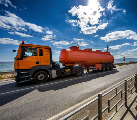 semitruck: The orange road tanker is moving along the highway under the clouds and the blue sky Stock Photo