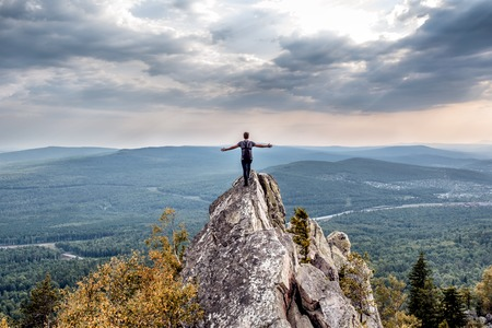 A young man on a mountain peak. Hands to both sides. Concept of freedom and absence of limitations. South Urals. Alexandrovskaya Sopka.