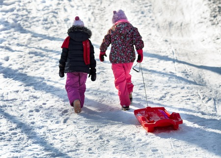 Two girls go uphill with sledges. Winter sledding. Outdoor games