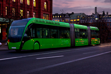 A green modern bus is moving in the city in the evening. People returning homes, traffic, night motion, the concept of modern, comfortable transport. Stock Photo