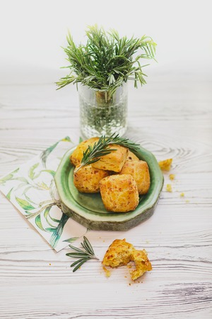 Scone with carrot is a traditional English pastry for afternoon tea or coffee breaks. Delicious buns are ready for maintenance on a wooden table. Scones with macro concept 写真素材