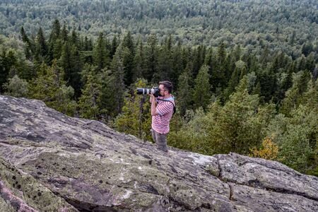 A man stands on a rock and shoots. Journey to the mountains with a camera. Concept travel, freedom, design. The Ural Mountains.