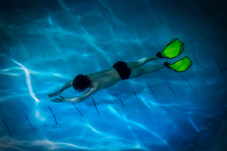 Boy-swimmer, participant in underwater struggle - aquatlon, swims under water in a swimming pool.