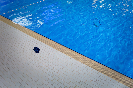 Pair of beach slippers lies on the edge of a swimming pool. Stok Fotoğraf - 96841613