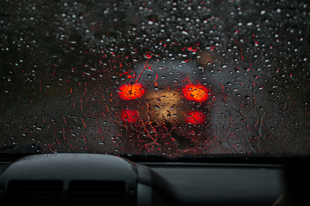 Vista desde un parabrisas empapado de lluvia en las luces traseras borrosas de un automóvil en el frente. Lluvia Pesada Foto de archivo