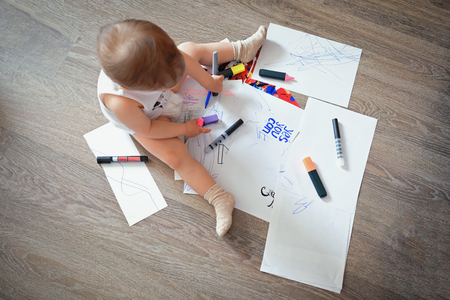2-year old child is sitting on the floor and paints with markers and pencils on scattered sheets of paper