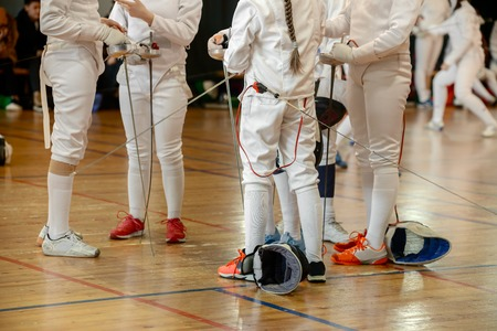 Girls, participants in fencing competitions on swords stand in the center of fencing hall waiting for beginning of the fight. Fencing masks on the floor, swords in their hands.