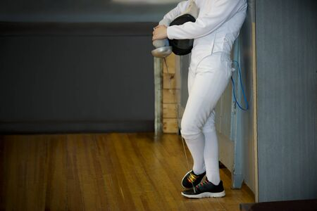 Girl athlete, participant in fencing competitions on swords is waiting next competition on the gym floor