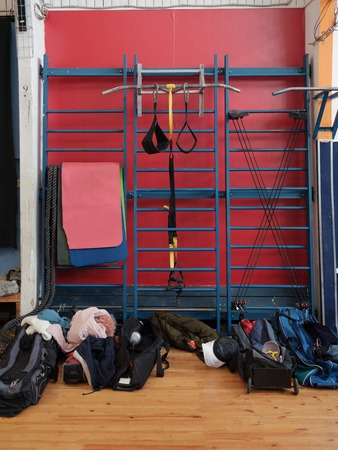 Sports equipment and gymnastics mats hang on the wall bars in the gym. Near the wall bars are bags of sportsmen - fencers. Chaos, locker room Banque d'images