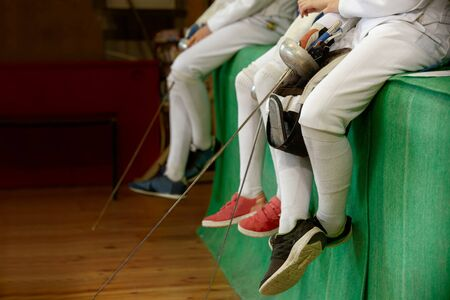 Girls athletes, participants in fencing competitions on swords rest between competitions. Athletes are sitting with masks and swords