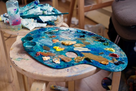 Color palette of the artist is on the table in the art studio. Around are scattered tubes of paint