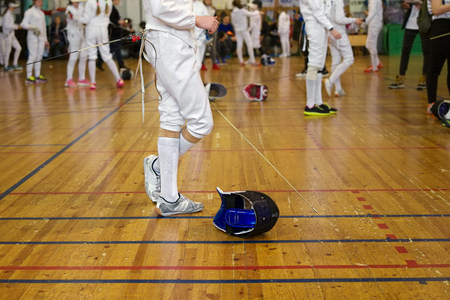 Girl participant in the fencing competition on swords is in the center of gym holding a sword in her hand, waiting for next battle. Fencing mask is on the floor 免版税图像