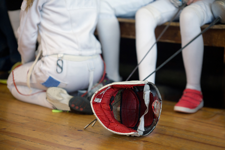 Girls participant in the fencing competition on swords sit on a bench holding a sword in her hand, waiting for next battle. Fencing mask is on the floor near girls Banque d'images