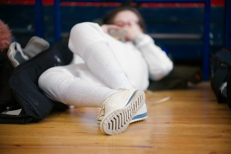Girls athlete, participant in fencing competitions on swords rests between competitions on the gym floor. She is looking on her mobile phone