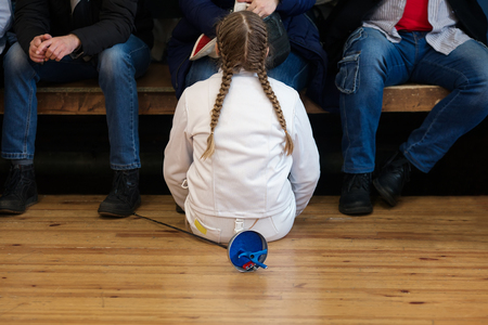 Girl athlete, participant in fencing competitions on swords rests between competitions. She seats behind her parents and fans on the gym floor