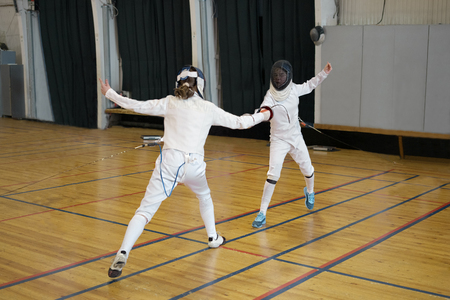 Girls, participants in fencing competitions are fighting on swords, epees. One girl is pricking another with a sword, epee